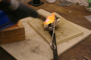 gently rock the crucible side to side to help melting the silver